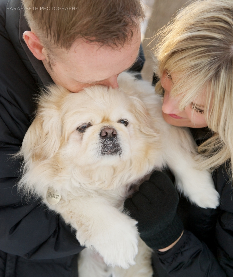 man and woman kissing pekinese dog